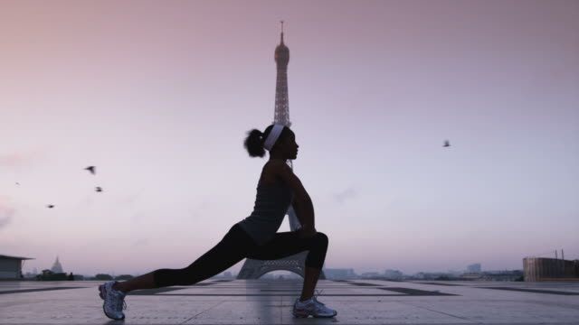 woman stretching and exercising in front of the eiffel tower - morning exercise stock videos & royalty-free footage