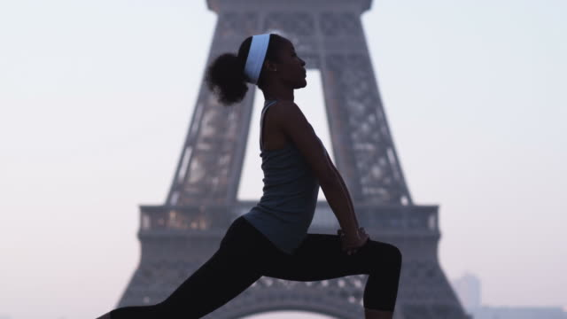 woman stretching and exercising in front of the eiffel tower - エッフェル塔点の映像素材/bロール