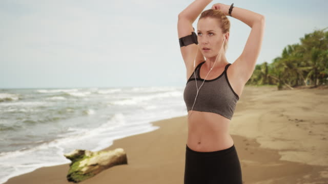 Woman stretching at the beach before running