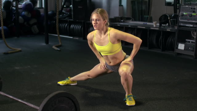 a woman stretching at the gym. - slow motion - legs apart stock videos & royalty-free footage