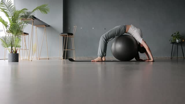 woman stretching back using fitness ball - fitness ball stock videos & royalty-free footage