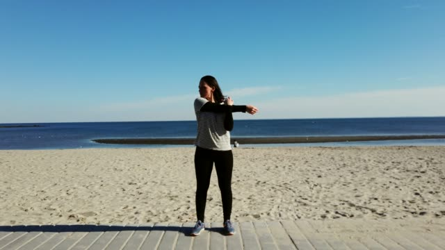 ビーチで彼女の腕を伸ばす女性 - 全身点の映像素材/bロール