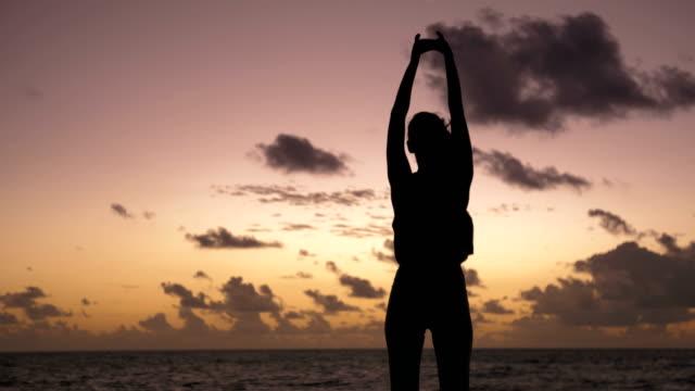 vídeos de stock, filmes e b-roll de mulher que estica seu corpo no por do sol - equilíbrio