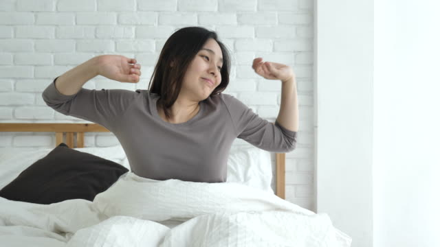 woman stretching in bed after wake up in morning - happy morning stock videos & royalty-free footage