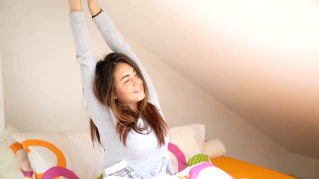 woman stretching in bed after wake up - svegliarsi video stock e b–roll