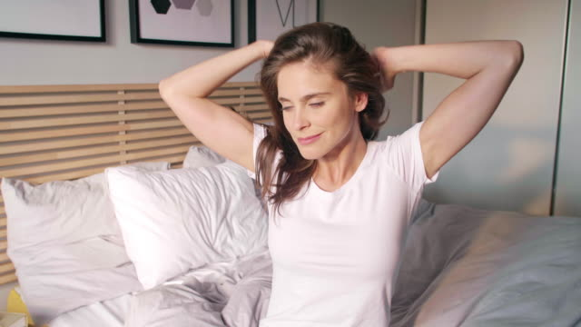 woman stretching in bed/ chorzow/ poland - waking up stock videos & royalty-free footage