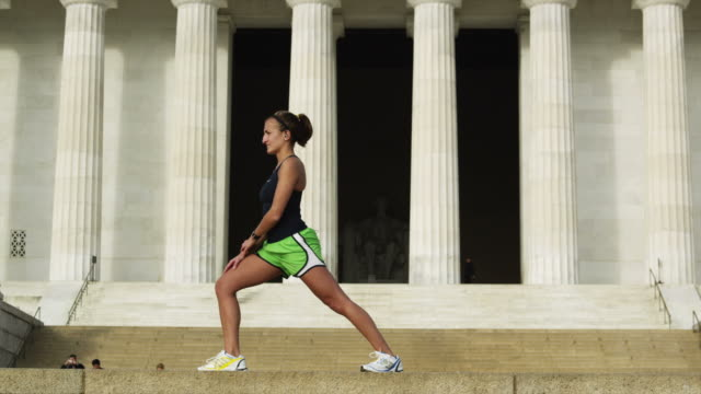 WS Woman stretching in front of Abraham Lincoln Memorial, Washington D.C, USA
