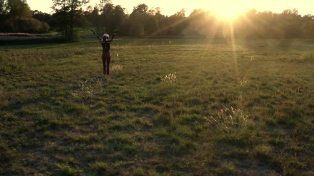 stockvideo's en b-roll-footage met woman stretching in green field at sunset - bukken