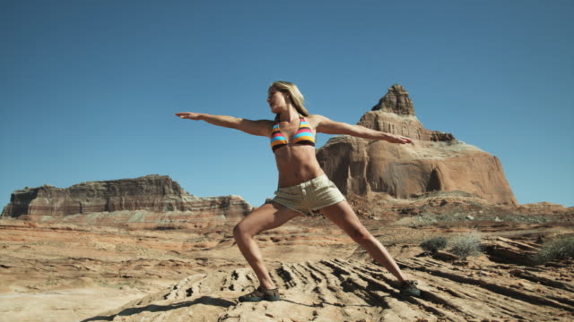 vídeos de stock e filmes b-roll de woman stretching in the desert - lago powell