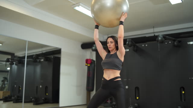 woman stretching in the gym - pallone per fitness video stock e b–roll