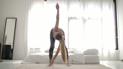 vídeos y material grabado en eventos de stock de mujer estirándose por la mañana - yoga