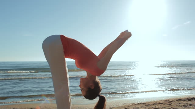 Woman stretching on beach/Marbella region, Spain