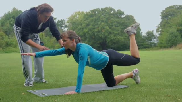 ms woman stretching on exercise mat with personal trainer in park, london, england - allenatore video stock e b–roll