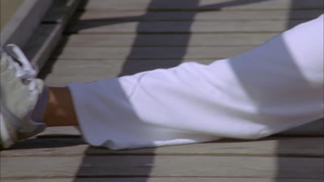 cu pan woman stretching on wooden footbridge, ryd, smaland, sweden - ノースリーブトップ点の映像素材/bロール