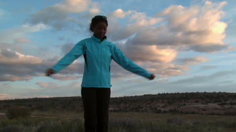 woman stretching outdoors with blue sky and clouds - see other clips from this shoot 1147 stock videos & royalty-free footage