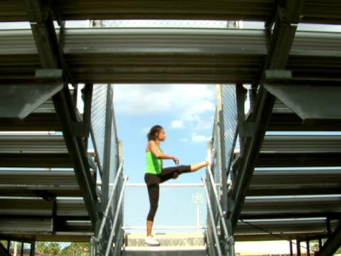 ms,  la,  woman stretching standing by stadium bleachers entrance,  side view,  miami,  florida,  usa - solo una donna di età media video stock e b–roll