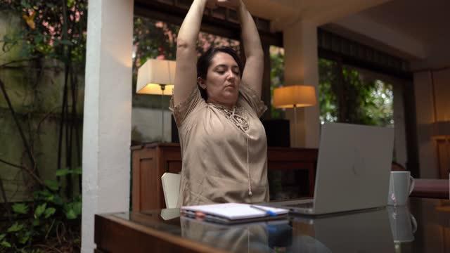 stockvideo's en b-roll-footage met vrouw die zich uitrekt terwijl het werken thuis - menselijke arm