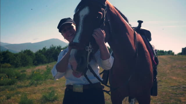 vídeos de stock, filmes e b-roll de woman strokes a horse - acariciando