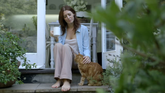 stockvideo's en b-roll-footage met woman stroking cat while drinking coffee outside home. - alleen één mid volwassen vrouw