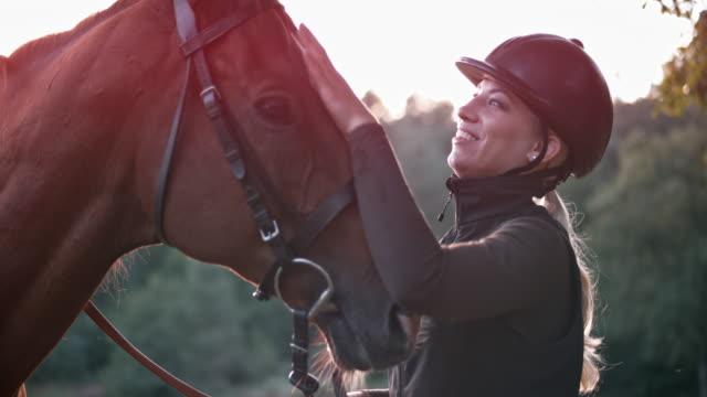 slo mo woman streichelt ihr braunes pferd - helm stock-videos und b-roll-filmmaterial