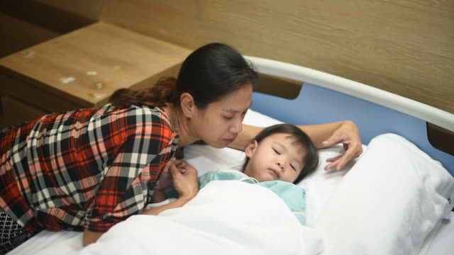 Woman stroking the little girl's head at the hospital , Sick little girl sleeping on the bed and waking up.