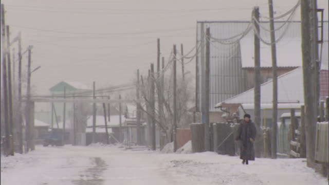 vidéos et rushes de a woman strolls through snow on a street lined with utility poles in russia. - fédération de russie