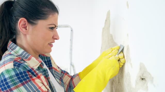 woman struggling to remove old paint. - negative emotion stock videos & royalty-free footage