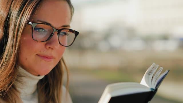 stockvideo's en b-roll-footage met een vrouw die buiten op universitaire campus studeert - sunny
