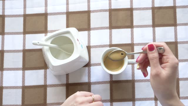 woman sugaring and stirring an espresso, from above - stirring stock videos & royalty-free footage