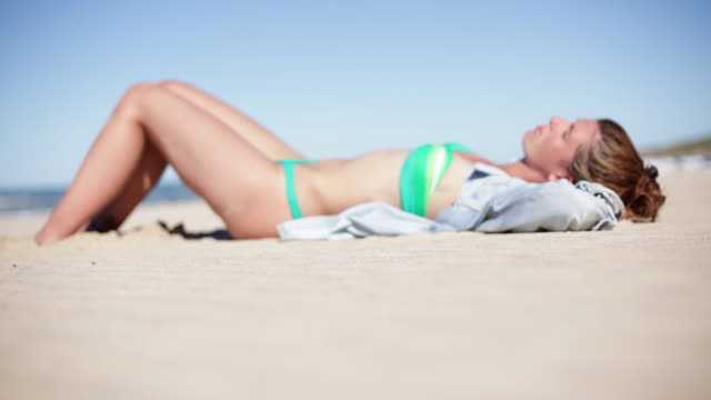 woman sunbathing on beach - sunbathing stock videos and b-roll footage
