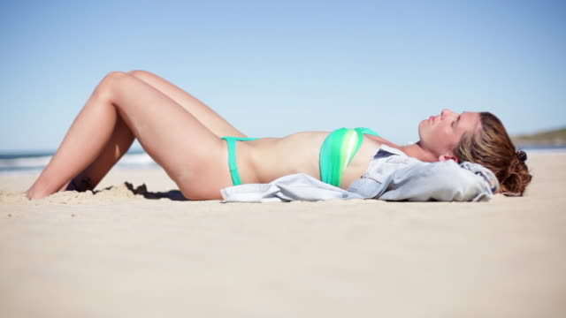 woman sunbathing on beach - zurücklehnen stock-videos und b-roll-filmmaterial