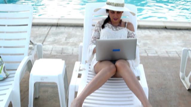 vídeos y material grabado en eventos de stock de mujer tomando el sol en sillas de playa con capacidad para una computadora portátil - tumbona