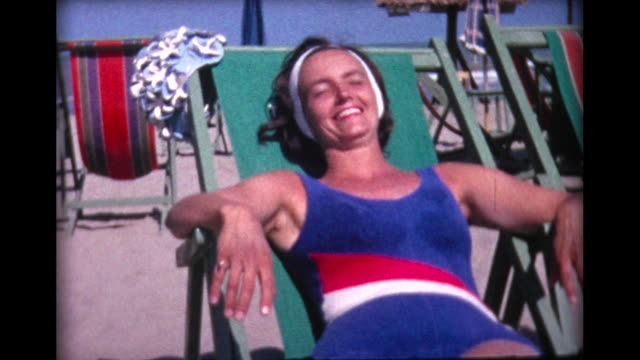 1964 woman sunbathing on lido beach - braun stock-videos und b-roll-filmmaterial