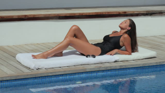 vidéos et rushes de ws woman sunbathing on poolside / andratx, mallorca, spain - rebord de piscine