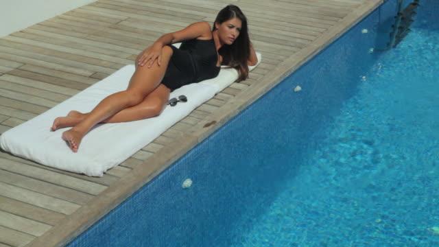 ws ha woman sunbathing on poolside / andratx, mallorca, spain - 横向きに寝る点の映像素材/bロール