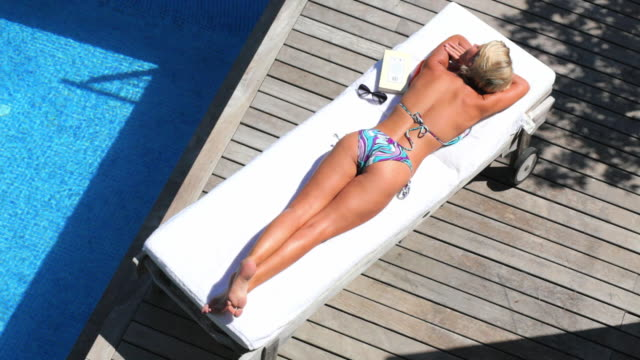 ws ha woman sunbathing on poolside / andratx, mallorca, spain - outdoor chair stock videos & royalty-free footage