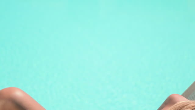 vídeos de stock e filmes b-roll de woman sunbathing on sunlounger at poolside - encostado