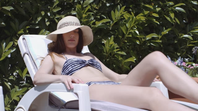 Woman sunbathing wearing straw hat