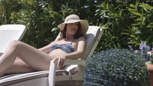 woman sunbathing wearing straw hat - frankreich stock-videos und b-roll-filmmaterial