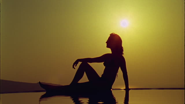 vídeos de stock, filmes e b-roll de ws woman sunbathing while rippled water reflects her shadow / santorini, greece - lago infinito