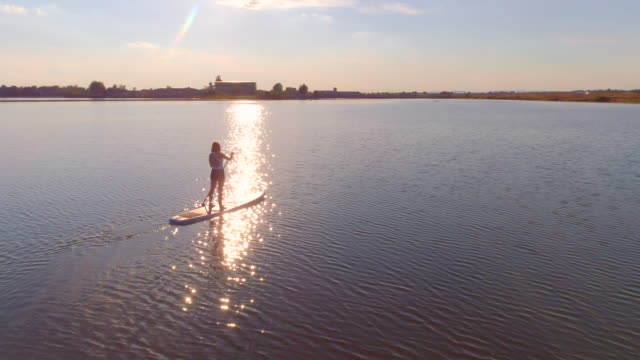 AERIAL Woman SUP boarding on a lake at sunset