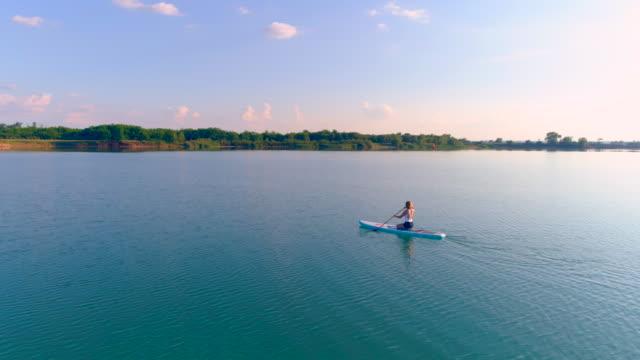 stockvideo's en b-roll-footage met luchtfoto vrouw sup instappen op een meer bij zonsondergang - peddelen