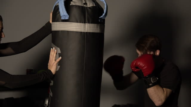 stockvideo's en b-roll-footage met woman supporting punching bag as man hits with boxing gloves - stootzak fitnessapparatuur