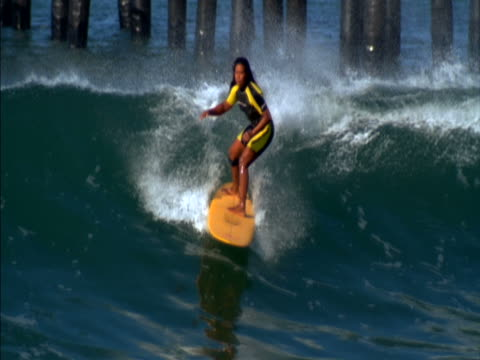 woman surfing a wave, slow motion - wetsuit stock videos & royalty-free footage