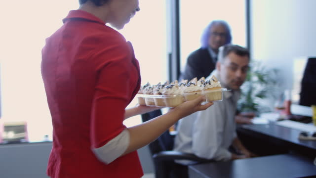woman surprising colleagues with cupcakes - office politics stock videos & royalty-free footage