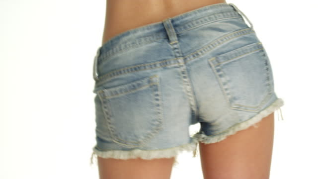 woman swaying hips in denim shorts - shorts stock-videos und b-roll-filmmaterial