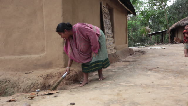 woman sweeping around her house with kid playing around, settlement not far from sreemangal (srimangal), division of sylhet, bangladesh, indian sub-continent, asia - bangladesh stock videos & royalty-free footage