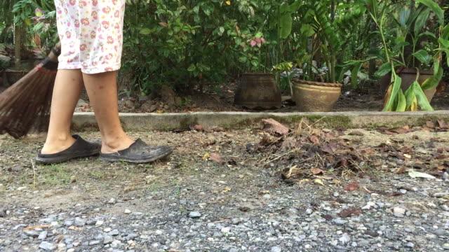 woman sweeping dried leafs on walkway - sweeping stock videos & royalty-free footage