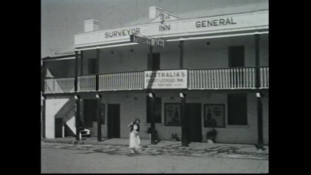 Woman sweeping street out the front of the 'Surveyor General Inn' / cu sign saying 'Australia's Oldest Licensed Inn ext 1834' / Internal Barman...