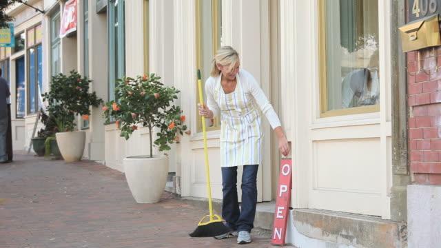 MS PAN Woman sweeping street outside shop, Petersburg, Virginia, USA